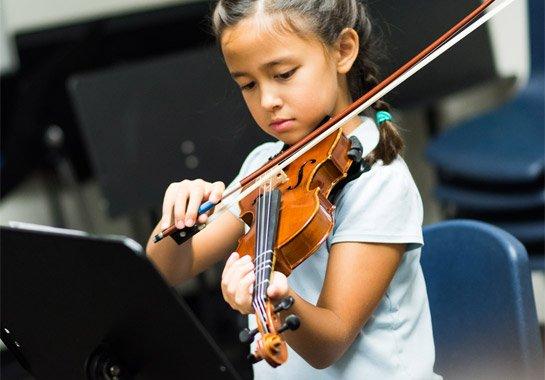 girl playing violing at school
