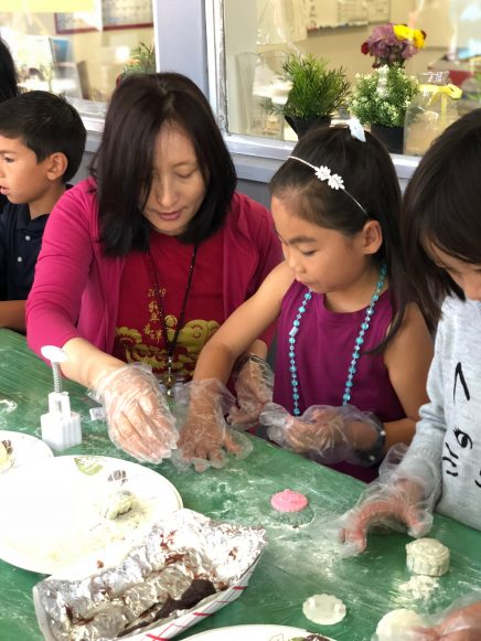 Children and teacher making cookies