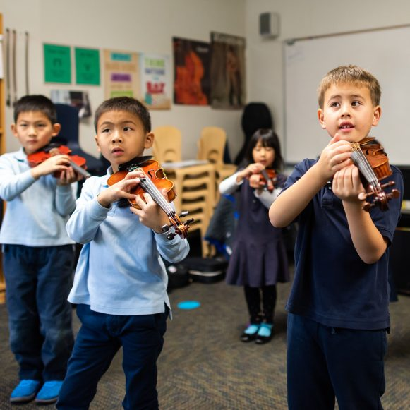 children learning to play violin